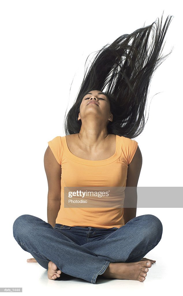 an ethnic female teenager in jeans and an orange shirt sits down and flips up her hair : Stockfoto