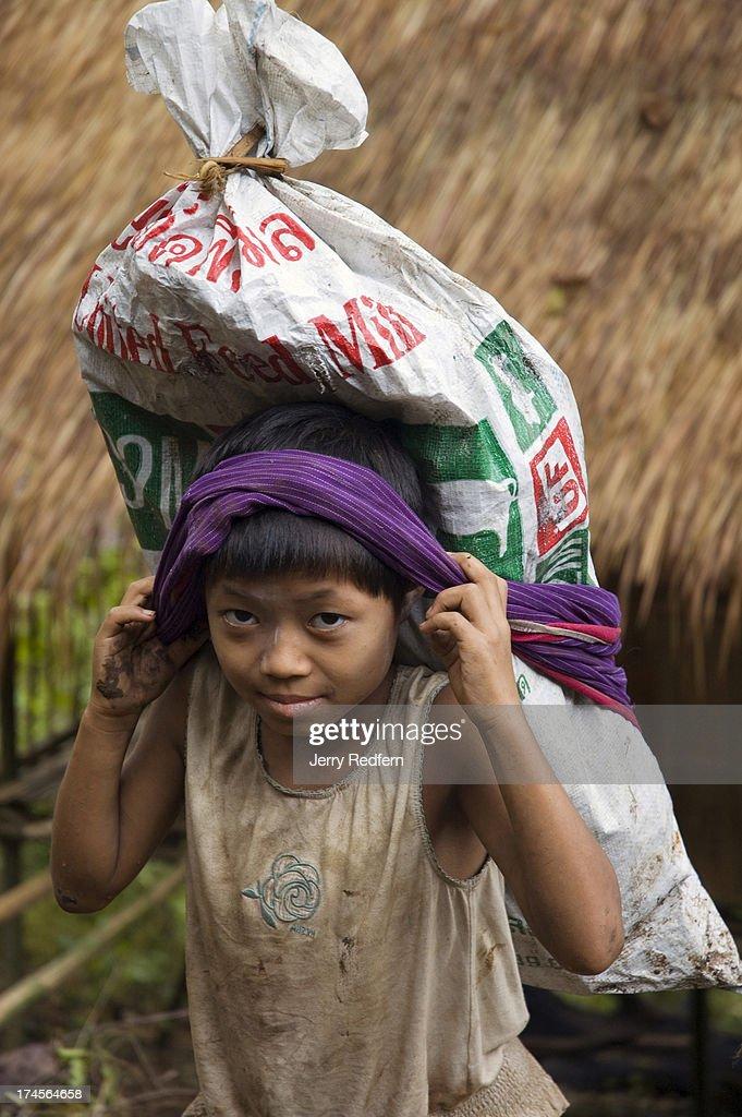 An Ethnic Karen Girl Carries Building Supplies Up The Steep
