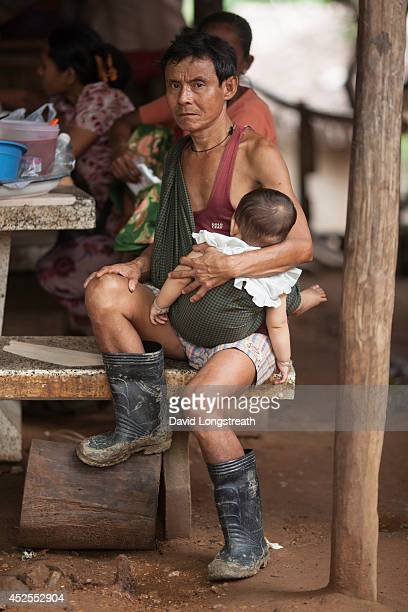 An ethnic Karen refugee father waits to see a doctor with her baby at a makeshif border clinic Currently there are around 100000 refugees living in...