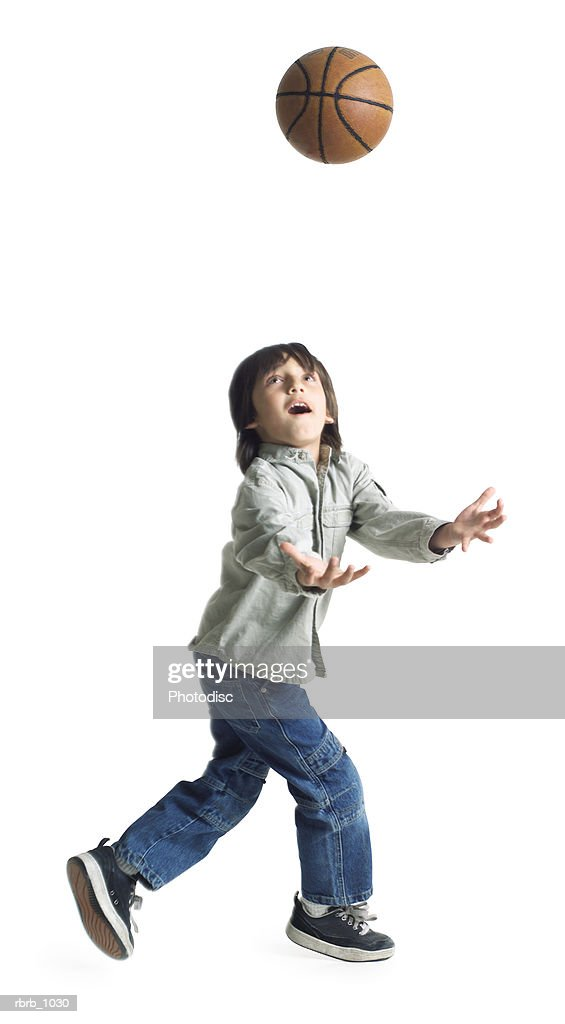 an ethnic liitle boy in runs and tries to catch a basketball pass : Stockfoto