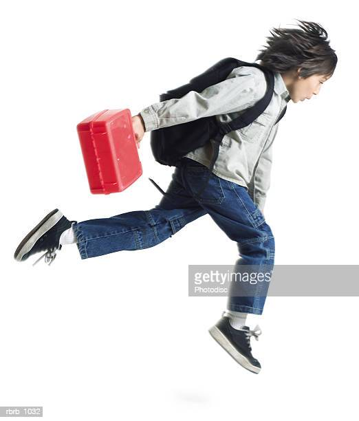 an ethnic little boy with a red lunchbox and a backpack runs along to school