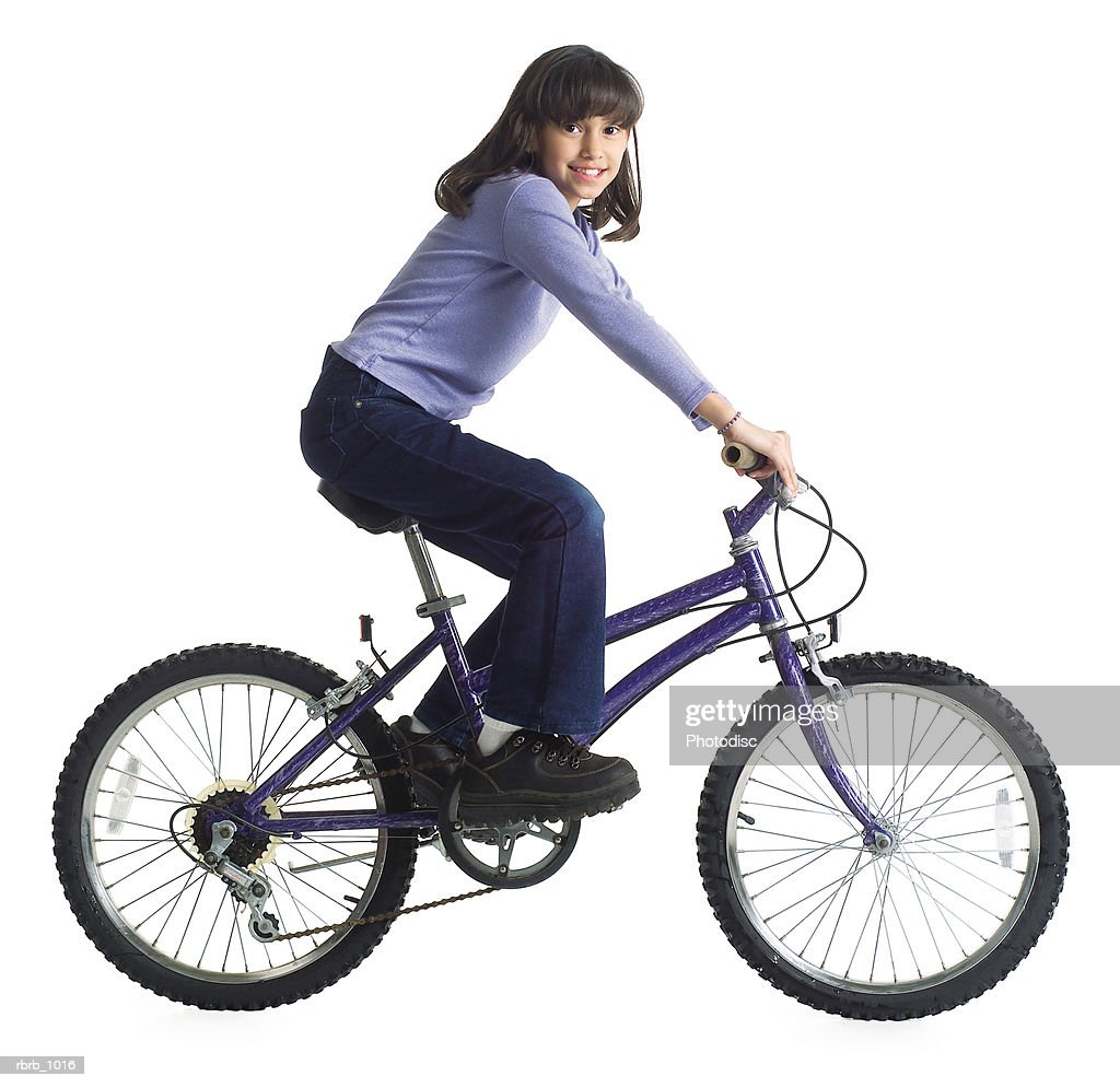 an ethnic little girl in jeans and a purple shirt rides her bicycle : Stockfoto