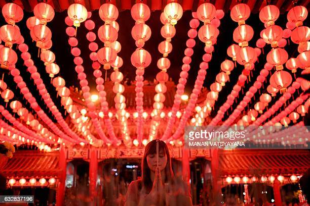 An Ethnic MalaysianChinese devotee burns josssticks at the Thean Hou temple decorated with red lanterns in Kuala Lumpur on January 27 2017 on the eve...