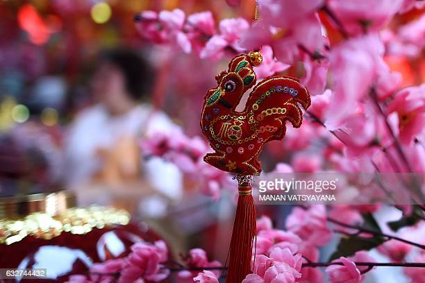An ethnic MalaysianChinese woman walks past a decoration of a rooster at a shop in Kuala Lumpur's Chinatown on January 26 ahead of the Lunar New Year...
