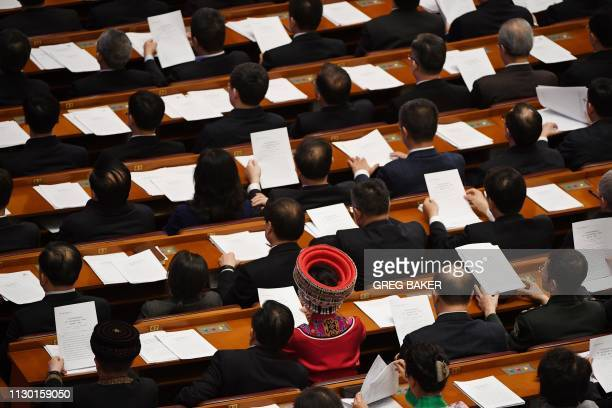 An ethnic minority delegate in traditional costume listens to speeches during the closing session of the Chinese People's Political Consultative...