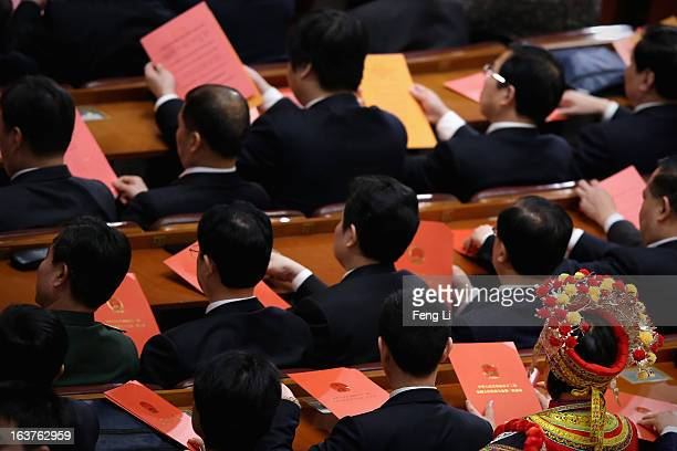 An ethnic minority delegate takes her vote during the fifth plenary meeting of the National People's Congress at the Great Hall of the People on...
