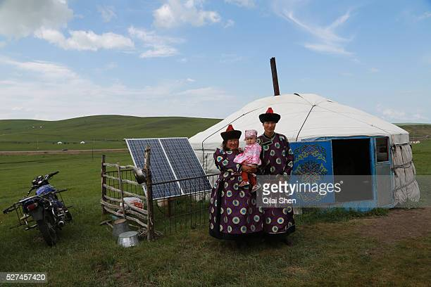 An ethnic mongolian family stands outside of their Yurt or traditional tent with their motorcycles and solar panel on the Hulunbuir or Hulunbeier...