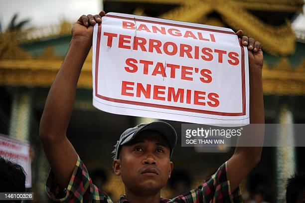 An ethnic Rakhine demonstrator holds a sign as hundreds gather at the Shwedagon pagoda after unrest flared in the western Myanmar state and at least...