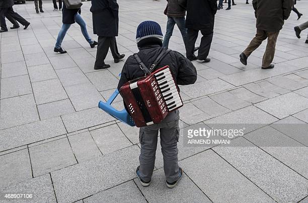 An ethnic Roma child counts his money after playing music for people on a small accordion on the main square of Pristina on April 8 2015 on...