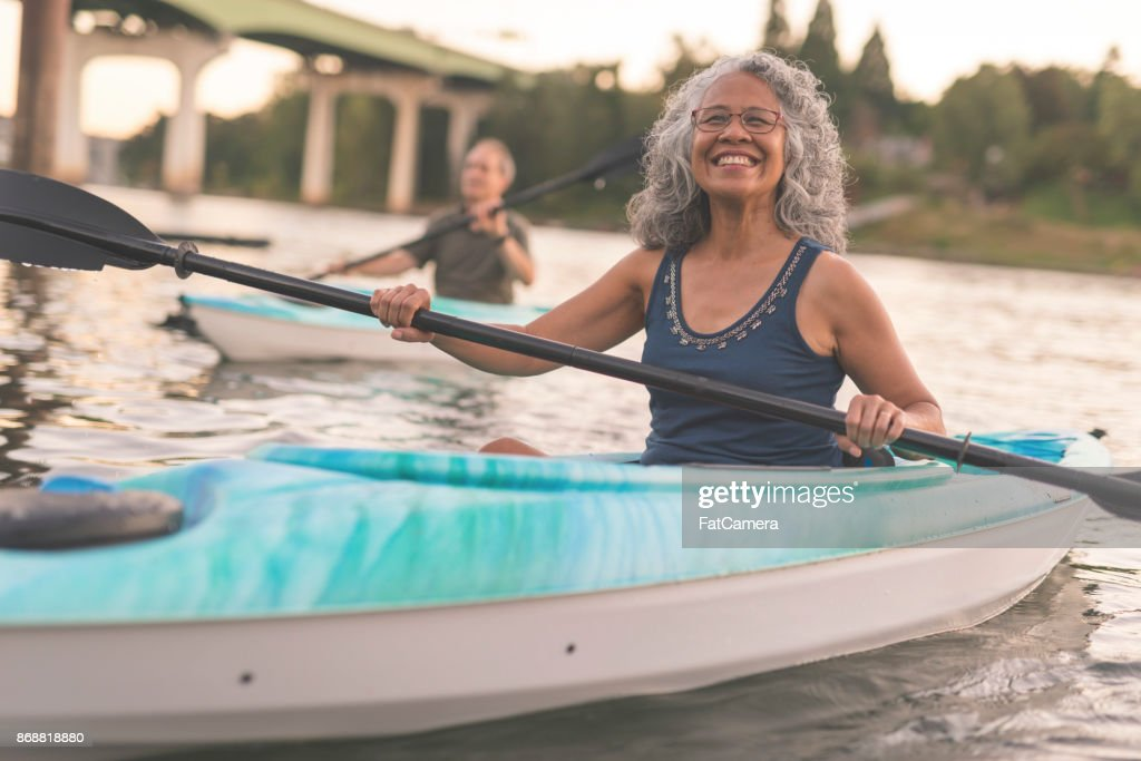 An ethnic senior woman smiles while kayaking with her husband : Stock Photo