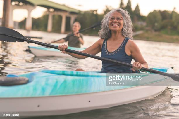 an ethnic senior woman smiles while kayaking with her husband - active senior woman stock photos and pictures