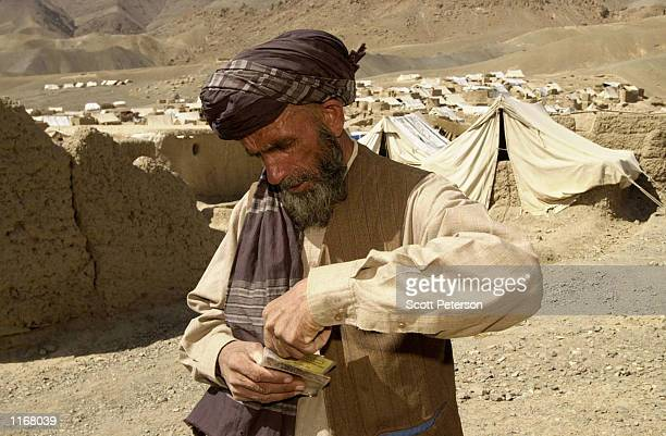 An ethnic Tajik fruit seller from Kabul Afghan Mir Ahmad pulls out his Red Cross prison registration card while in the Anaba Camp for displaced...