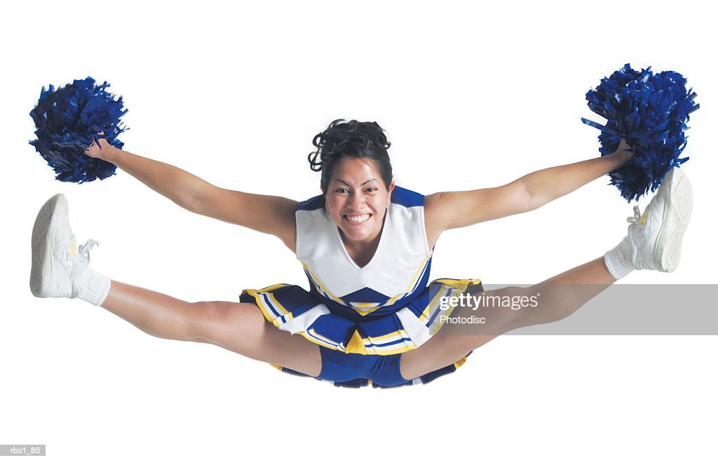 an ethnic teenage female cheerleader jumps high in the air and does the splits : Foto de stock