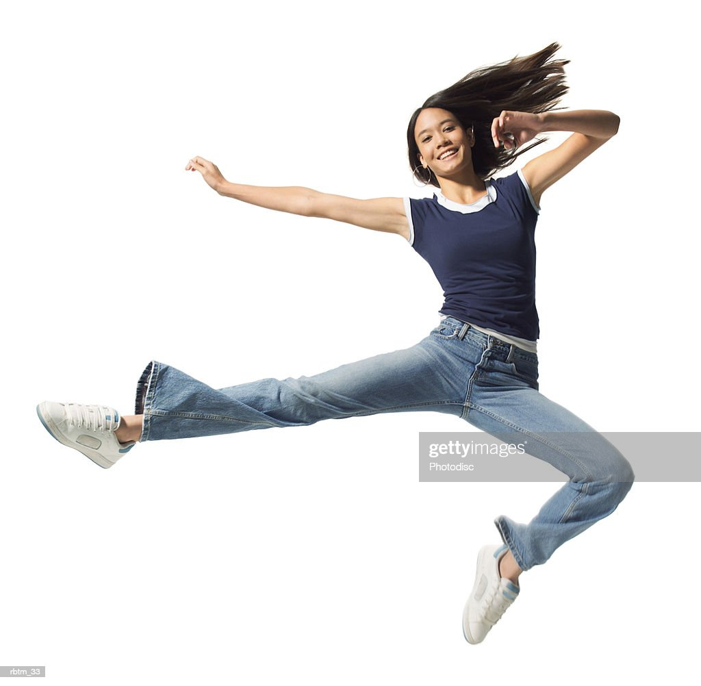 an ethnic teenage female in jeans and a blue tank top jumps through the air : Foto de stock