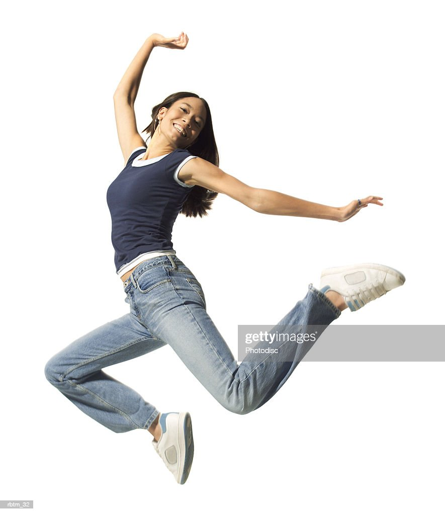 an ethnic teenage female in jeans and a blue tank top jumps up playfully in the air : Foto de stock