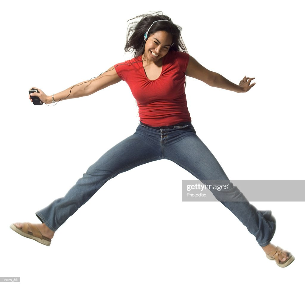 an ethnic teenage female in jeans and a red shirt jumps up while she listens to music : Foto de stock