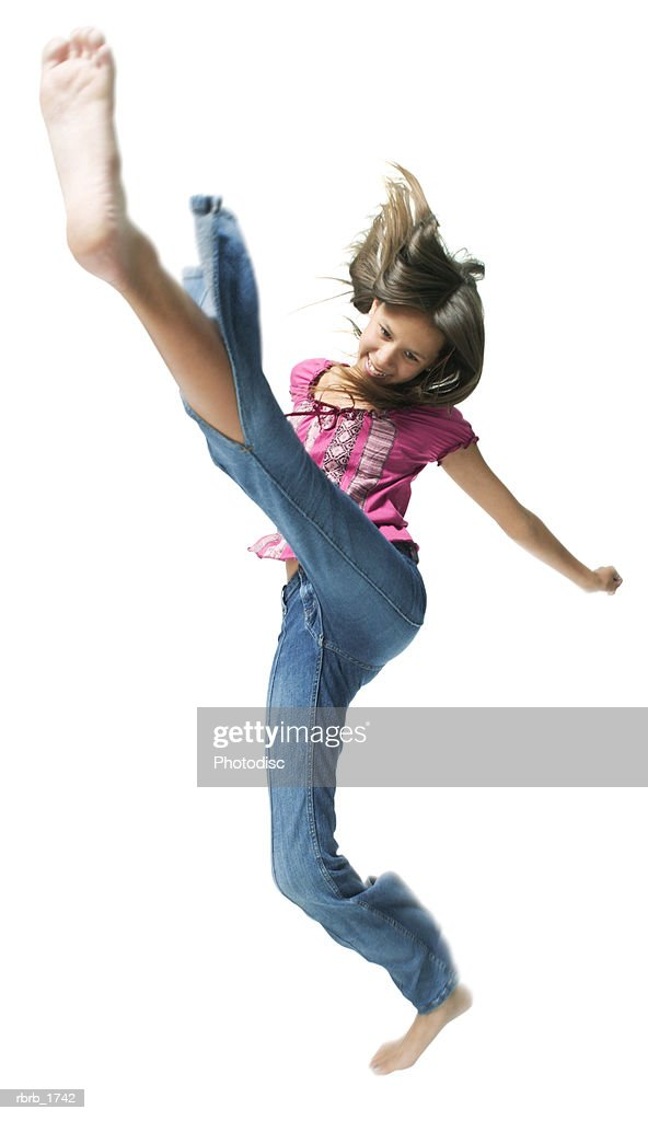 an ethnic teenage girl in jeans and a pink shirt jumps and kicks through the air : Stockfoto