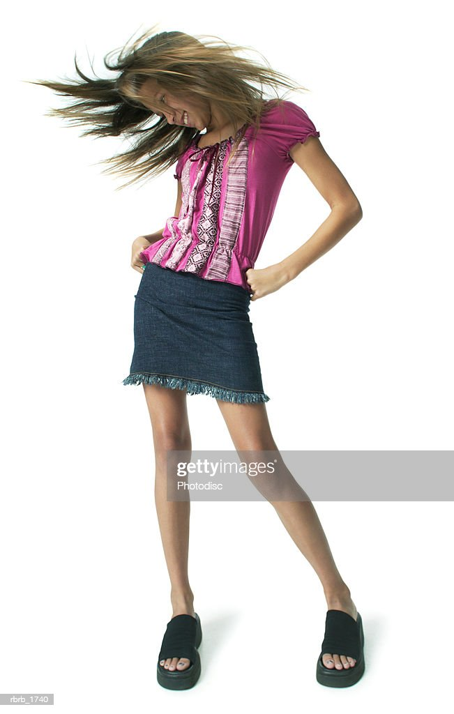 an ethnic teenage girl in jeans and a pink shirt tosses her hair around wildly : Stock Photo