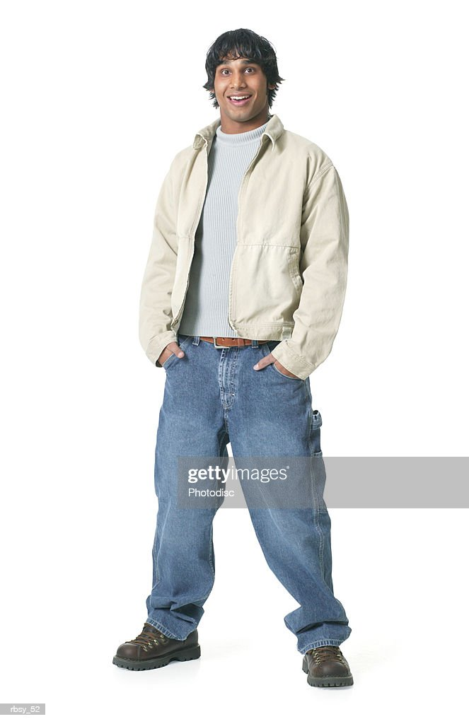 an ethnic teenage male in jeans and a tan jacket puts his hands in his pockets and smiles at the camera : Foto de stock