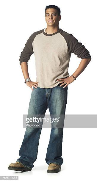 an ethnic teenage male in jeans and a tan shirt stands with a nice smile