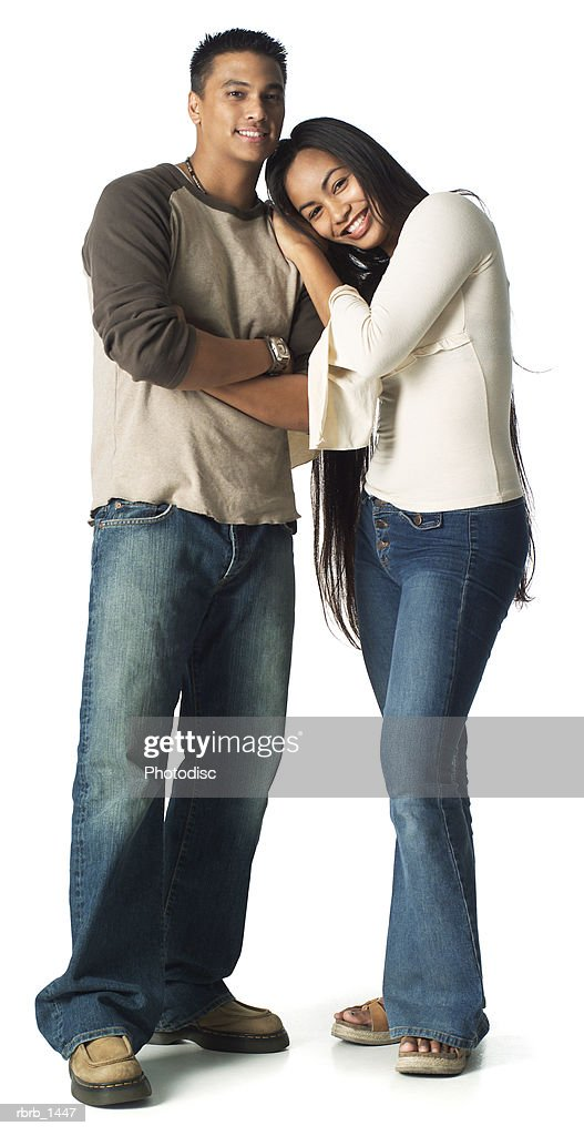 an ethnic teenage male in jeans and a tan shirt stands with his younger sister as they smile : Stock Photo