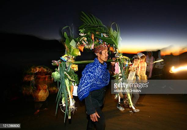 An ethnic Tengger man carries his offering during the Yadya Kasadha ceremony in the ancient volcano complex, the Tengger in Probolinggo, East Java on...