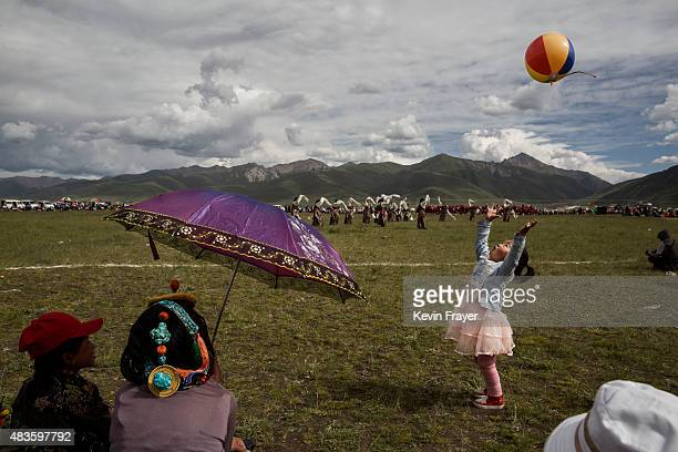 An ethnic Tibetan girl plays as nomads watch traditional dancing on July 25 2015 at a local government sponsored festival on the Tibetan Plateau in...