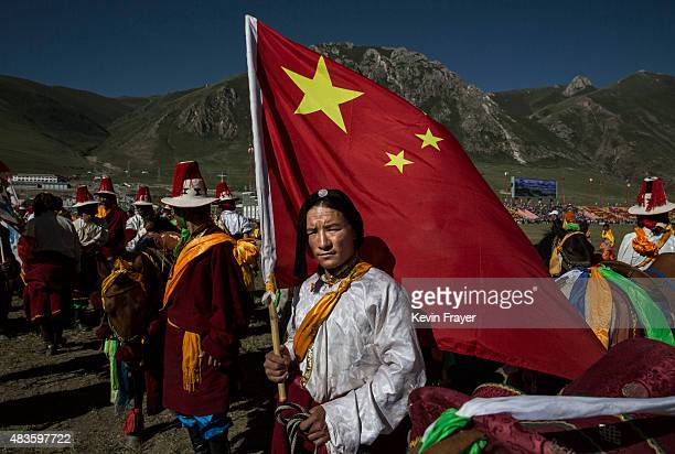 An ethnic Tibetan nomad in traditional dress holds a Chinese flag as he waits to perform horse skills on July 24 2015 at a local government sponsored...