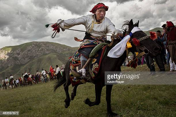An ethnic Tibetan nomad performs skills during a riding competition at a local festival on July 26 2015 on the Tibetan Plateau in Yushu County...