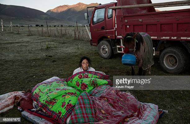 An ethnic Tibetan nomad sits up after sleeping outside next to his horse before racing at a local government sponsored festival on July 26 2015 on...