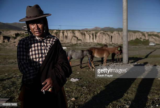 An ethnic Tibetan nomad stands with his horses before racing at a local government sponsored festival on July 26 2015 on the Tibetan Plateau in Yushu...