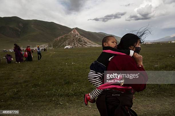 An ethnic Tibetan woman carries her child on July 25 2015 at a local government sponsored festival on the Tibetan Plateau in Yushu County Qinghai...