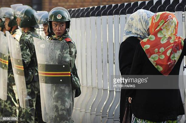 An ethnic Uigur women look through a security fence to the Grand Bazaar which remains closed as Chinese soldiers look on in Urumqi in China's farwest...