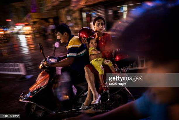 An ethnic Uyghur family ride a scooter on June 28, 2017 in the old town of Kashgar, in the far western Xinjiang province, China. Kashgar has long...