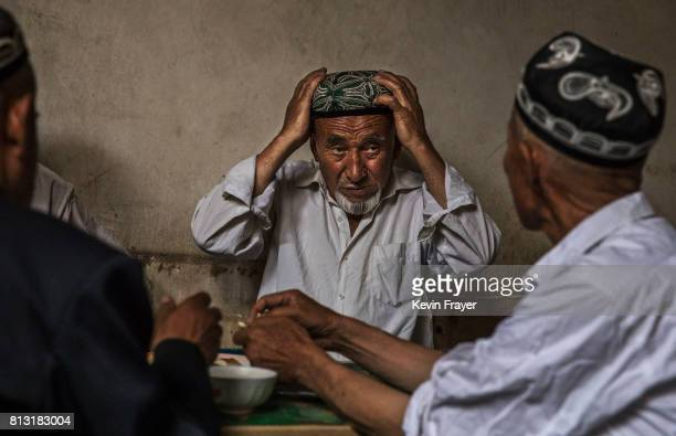 An ethnic Uyghur man adjust his traditional hat called a doppa as he talks with others at a teahouse on July 1 2017 in the old town of Kashgar in the...