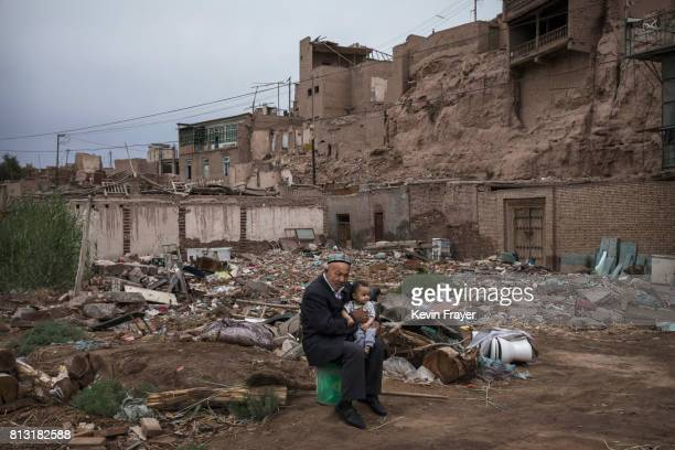 An ethnic Uyghur man holds his grandson as he sits outside his house in an area waiting development by authorities on June 28 2017 in the old town of...