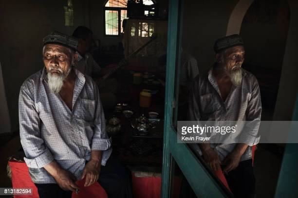An ethnic Uyghur man sits in a local teahouse on June 29 2017 in the old town of Kashgar in the far western Xinjiang province China Kashgar has long...