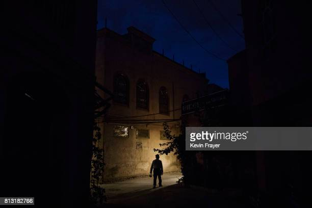 An ethnic Uyghur man walks in an alleyway near a local police station on June 27 2017 in the old town of Kashgar in the far western Xinjiang province...