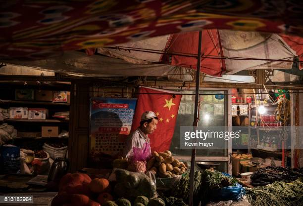 An ethnic Uyghur shopkeeper works next to a Chinese flag at his shop on June 29 2017 in the old town of Kashgar in the far western Xinjiang province...