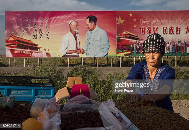 An ethnic Uyghur woman arranges raisins for sale at her stall with a billboard showing the late Communist Party leader Mao Zedong in the background...