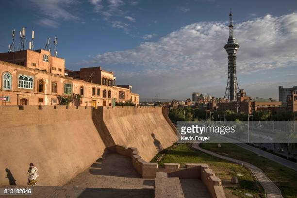 An ethnic Uyghur woman runs on a newly built section of the the old city wall that is part of a new development by authorities on June 27 2017 in the...
