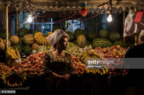 An ethnic Uyghur woman waits for customers at her fruit stand on June 27 2017 in the old town of Kashgar in the far western Xinjiang province China...