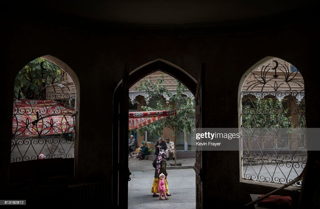 An ethnic Uyghur woman walks by the closed Islamic school on July 1, 2017 in the old town of Kashgar, in the far western Xinjiang province, China. Kashgar has long been considered the cultural heart of Xinjiang for the province's nearly 10 million Muslim Uyghurs. At an historic crossroads linking China to Asia, the Middle East, and Europe, the city has changed under Chinese rule with government development, unofficial Han Chinese settlement to the western province, and restrictions imposed by the Communist Party. Beijing says it regards Kashgar's development as an improvement to the local economy, but many Uyghurs consider it a threat that is eroding their language, traditions, and cultural identity. The friction has fuelled a separatist movement that has sometimes turned violent, triggering a crackdown on what China's government considers 'terrorist acts' by religious extremists. Tension has increased with stepped up security in the city and the enforcement of measures including restrictions at mosques.