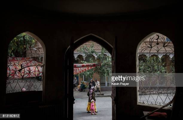 An ethnic Uyghur woman walks by the closed Islamic school on July 1 2017 in the old town of Kashgar in the far western Xinjiang province China...