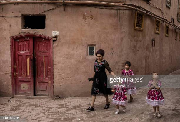 An ethnic Uyghur woman walks with her children on June 28 2017 in the old town of Kashgar in the far western Xinjiang province China Kashgar has long...