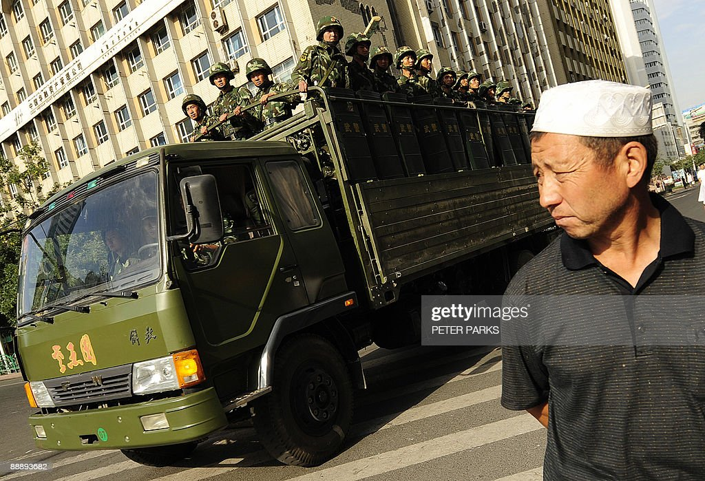 An Ethnic Uygur man watches as an army t : News Photo