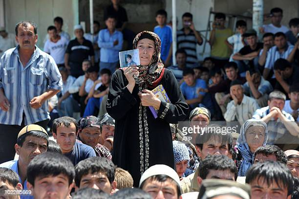 An ethnic Uzbek woman cries as she holds a photo of a killed relative during peace rally to call on ethnic Uzbeks to pull down a barricade between...
