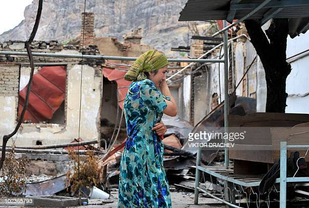 An ethnic Uzbek woman cries as she passes by a burnt-out house in the town of Osh on June 24, 2010. Almost all the refugees who fled Kyrgyzstan...