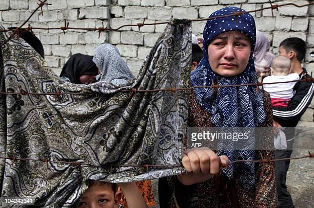 An ethnic Uzbek woman, cries as she waits at the Kyrgyz-Uzbek border outside the village of Suratash some 15kms south of Osh on June 14, 2010....
