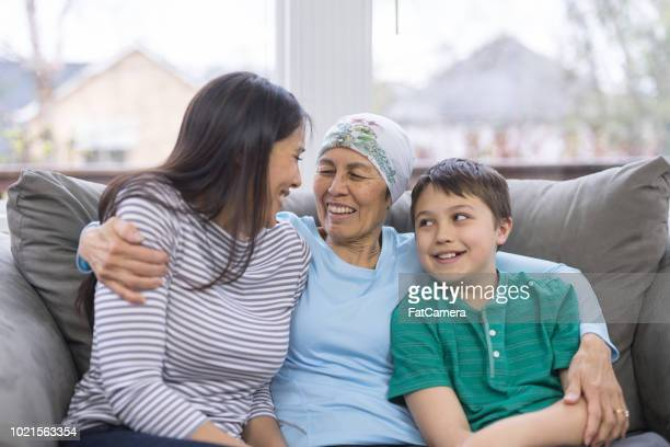 uma mulher étnica em seu 60 anos lutando contra o câncer senta-se alegremente com sua filha e neto no sofá - cancer illness - fotografias e filmes do acervo